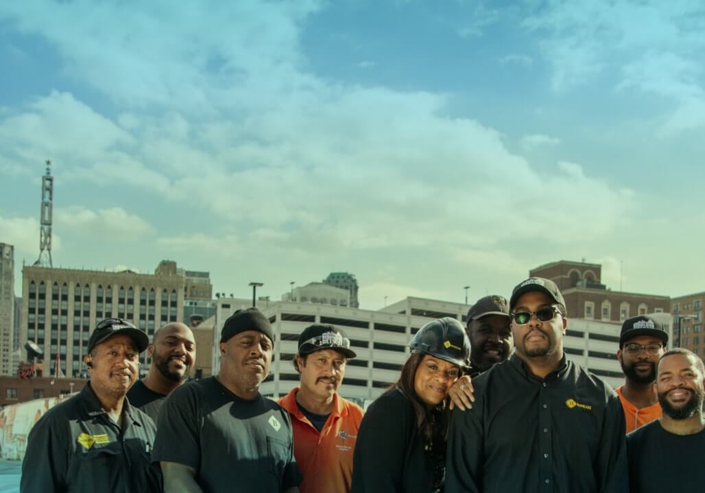 Nine people stand handled together, smiling at the camera, with downtown Detroit rooflines behind them, including the Fox Theatre. They are dressed casually in black and orange, with some sporting hard hats and safety googles.
